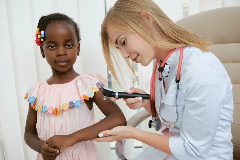 Doktor mit der medizinischen Ausrüstung, die wenigem Mädchen hilft lizenzfreie stockfotos