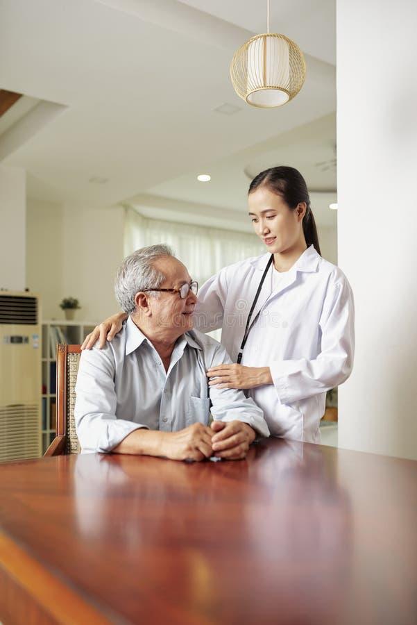 Doktor mit ihrem älteren Patienten stockbild