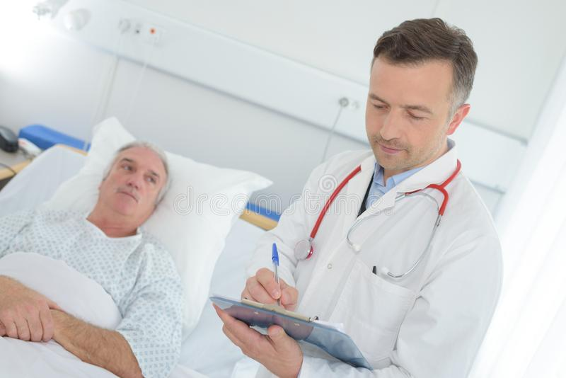 Doktor mit Klemmbrett älteren Patienten an der Krankenstation besuchend stockfotografie