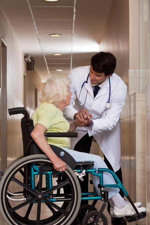 Doktor mit Patienten auf Rollstuhl stockbild