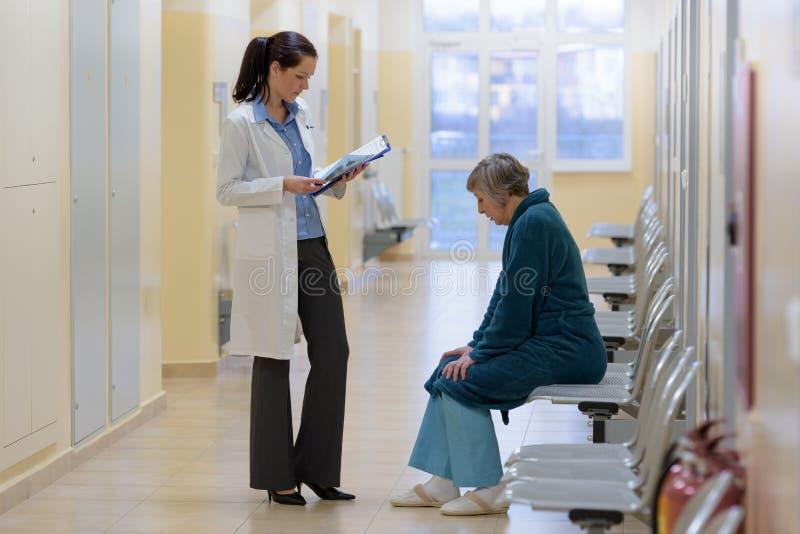 Doktor mit Patienten im Krankenhauskorridor stockfoto