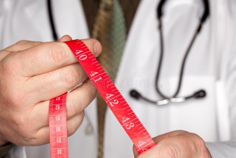 Doktor mit Stethoskop-Holding-messendem Band lizenzfreies stockfoto