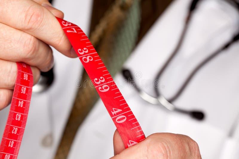 Doktor mit Stethoskop-Holding-messendem Band lizenzfreie stockbilder
