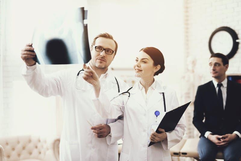 Doktor mit Stethoskop und Krankenschwester überprüft Röntgenstrahl des Geschäftsmannes, des Patienten lizenzfreie stockbilder