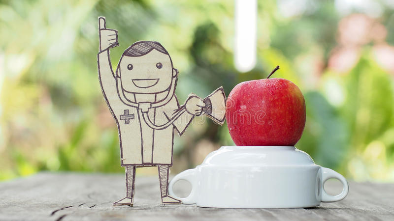 Doktor mit Stethoskopmaß auf einem Apfel stockfotografie