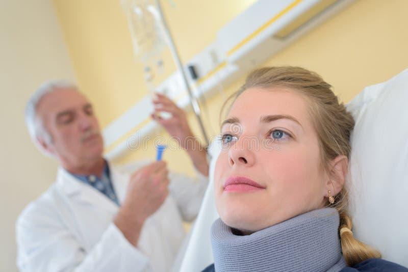Doktor mit tragender Halsklammer des Patienten im Krankenhauszimmer lizenzfreie stockfotografie