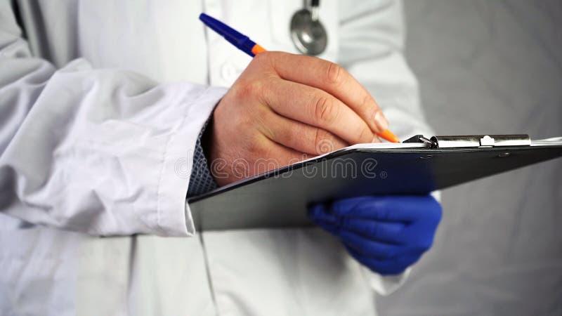 Doktor notiert die Ergebnisse der geduldigen Behandlung stockfotografie