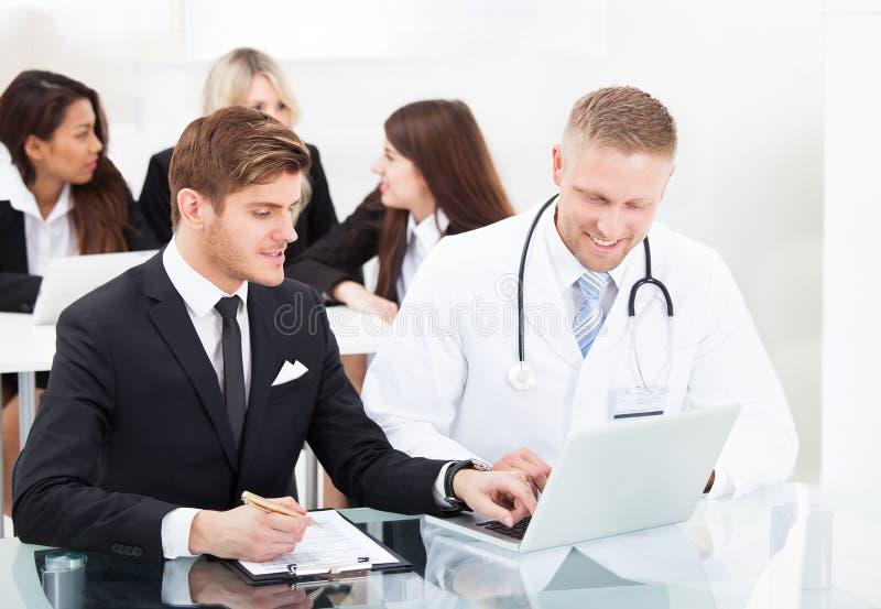 Doktor och affärsman som diskuterar över bärbara datorn royaltyfri foto