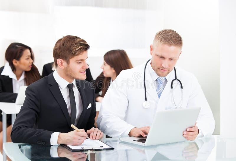 Doktor och affärsman som diskuterar över bärbara datorn royaltyfri bild