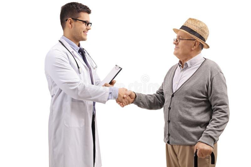 Doktor och en äldre patient som skakar händer arkivbild