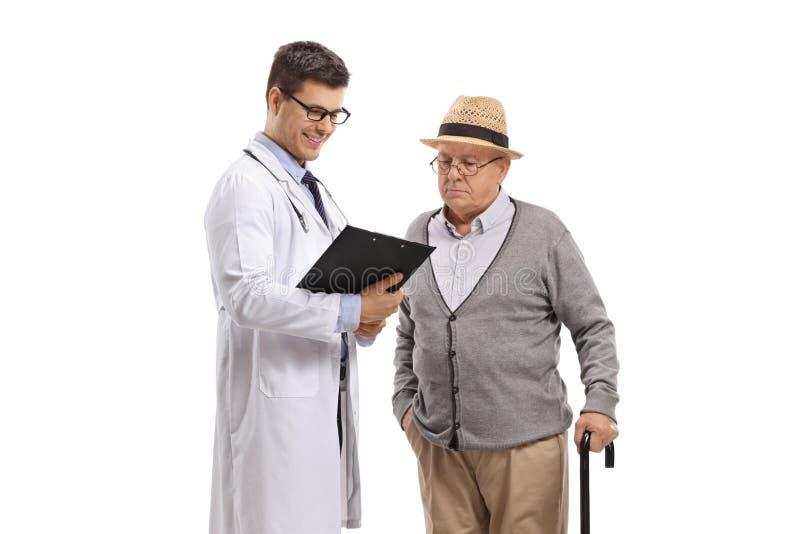 Doktor och en manlig h?g patient som ser en skrivplatta arkivfoto