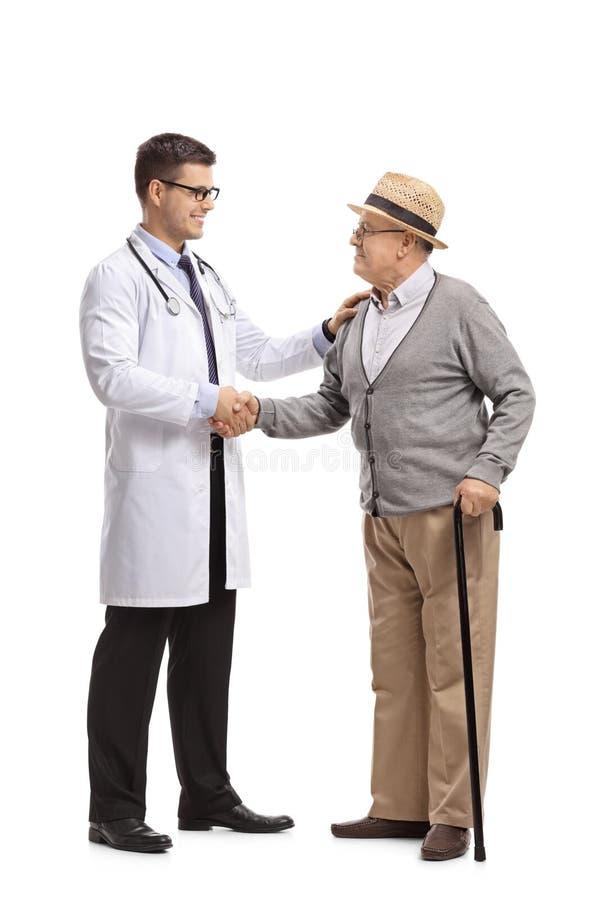 Doktor och en mogen man som skakar händer royaltyfria bilder
