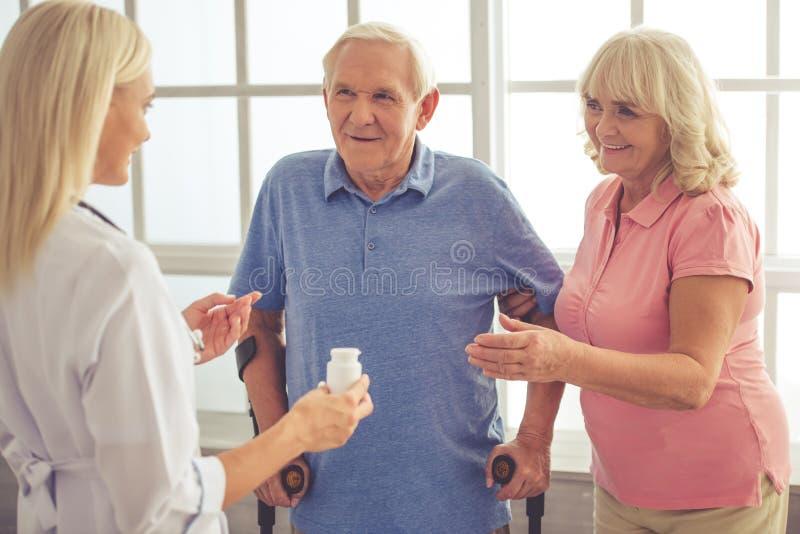 Doktor och gamla människor royaltyfri foto