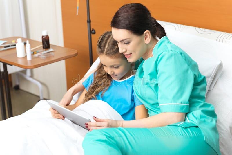 Doktor och liten flicka som använder den digitala minnestavlan och sitter på säng royaltyfri fotografi
