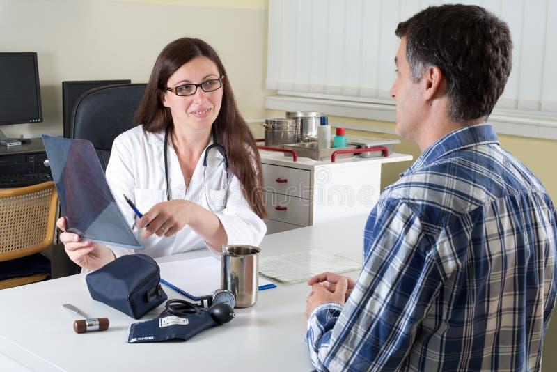 Doktor och mitt åldrades tålmodiga diskuterande lungaröntgenstråleresultat i konsulterande rum arkivbild