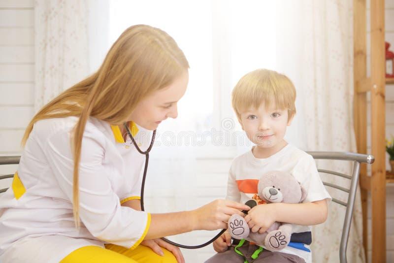 Doktor och patient hemma Lilla flickan undersöks av pediatriskt med stetoskopet royaltyfri fotografi