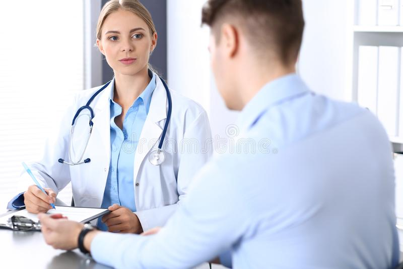 Doktor och patient i sjukhus Konsulterande affärsman för härlig blond läkare om hans hälsa stetoskop för pengar för begreppsliesm arkivfoton