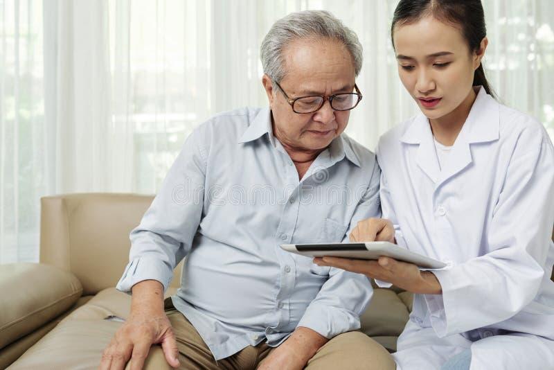 Doktor och patient som använder minnestavlaPC royaltyfri bild