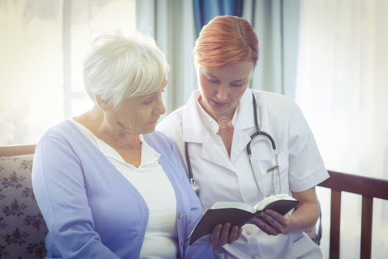 Doktor och patient som läser en bok royaltyfria foton