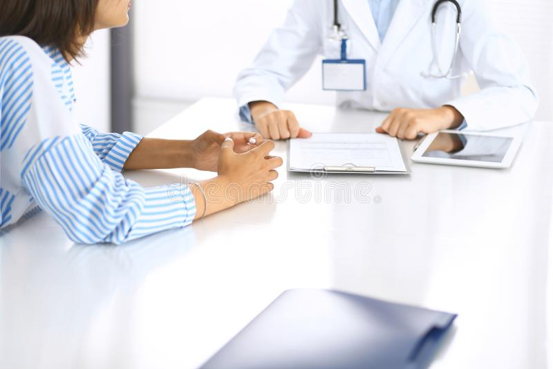 Doktor och patient som talar och diskuterar vård- behandling, medan sitta på skrivbordet, närbild care hälsomedicinen arkivbilder
