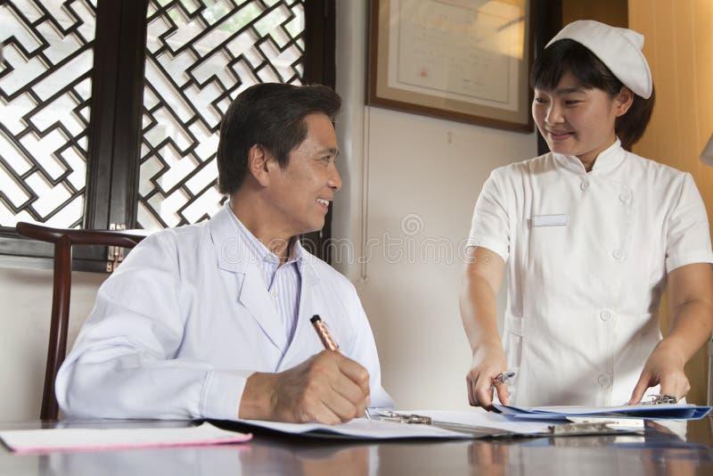 Doktor och sjuksköterska på skrivbordet royaltyfri bild
