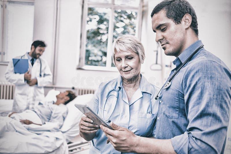 Doktor och sjuksköterska som använder den digitala minnestavlan royaltyfri bild