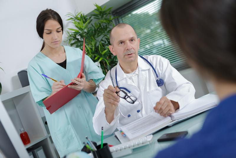 Doktor och sjuksköterska som diskuterar på kontoret royaltyfria bilder