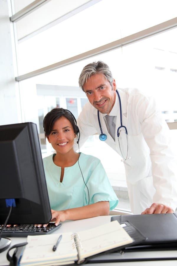 Doktor och sjuksköterska som i regeringsställning fungerar royaltyfria bilder