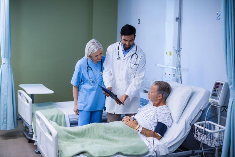 Doktor och sjuksköterska som undersöker en patient arkivfoto