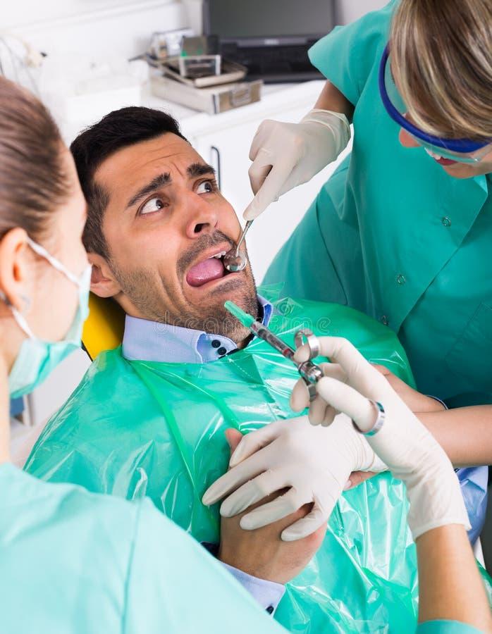 Doktor och skrämd patient på kliniken arkivfoto