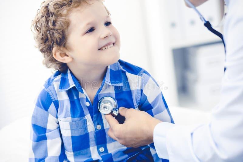 Doktor och t?lmodigt barn Unders?kande pys f?r l?kare Vanligt medicinskt bes?k i klinik care h?lsomedicinen royaltyfri bild