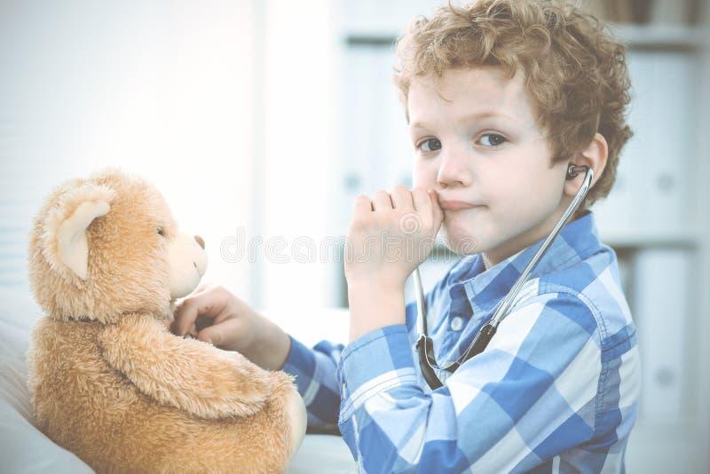 Doktor och t?lmodigt barn Unders?kande pys f?r l?kare Vanligt medicinskt bes?k i klinik care h?lsomedicinen arkivbilder