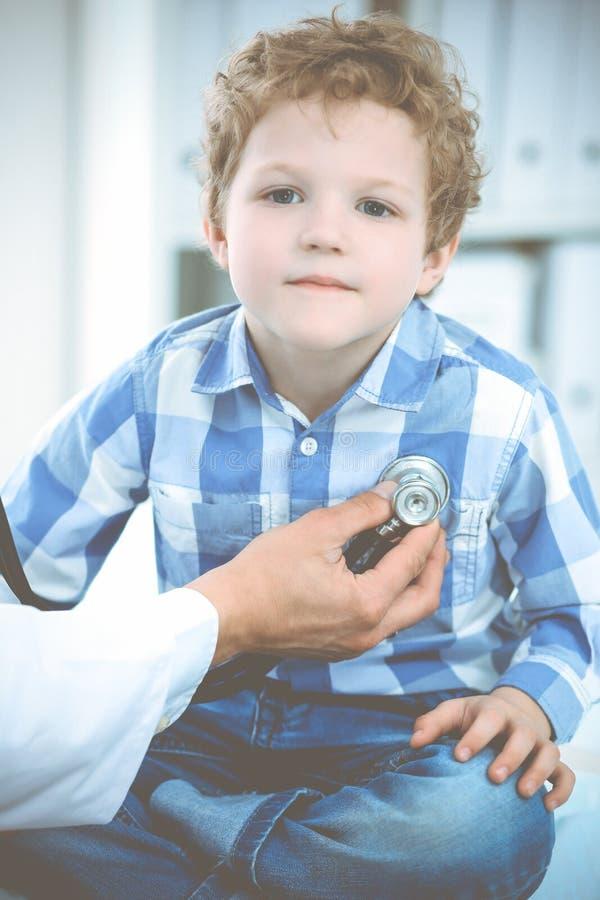 Doktor och t?lmodigt barn Unders?kande pys f?r l?kare Vanligt medicinskt bes?k i klinik care h?lsomedicinen royaltyfri fotografi
