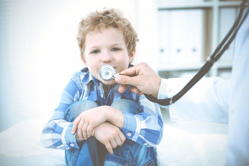 Doktor och t?lmodigt barn Unders?kande pys f?r l?kare Vanligt medicinskt bes?k i klinik care h?lsomedicinen royaltyfria foton