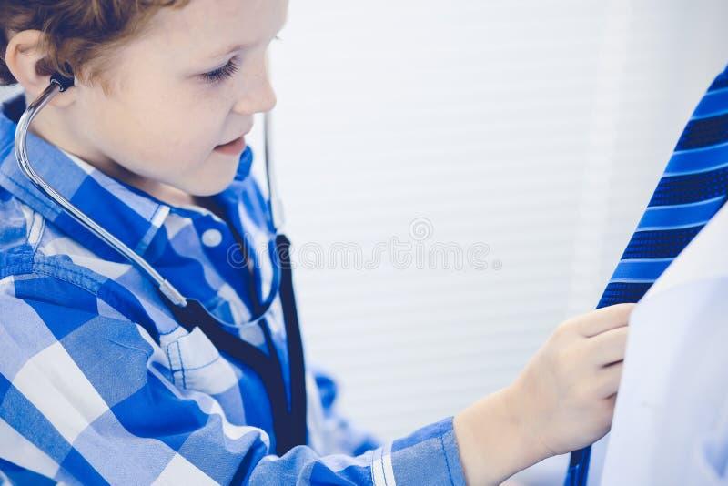 Doktor och t?lmodigt barn Unders?kande pys f?r l?kare Vanligt medicinskt bes?k i klinik care h?lsomedicinen arkivbild
