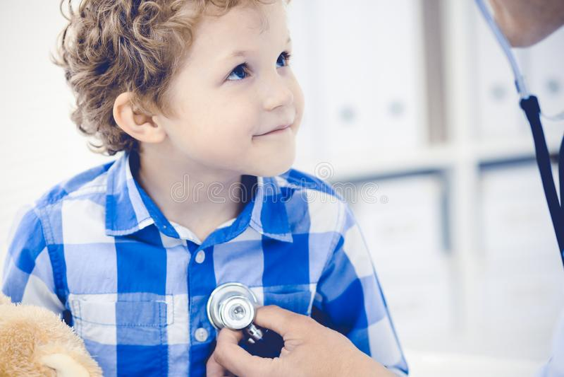 Doktor och t?lmodigt barn Unders?kande pys f?r l?kare Vanligt medicinskt bes?k i klinik care h?lsomedicinen arkivfoto
