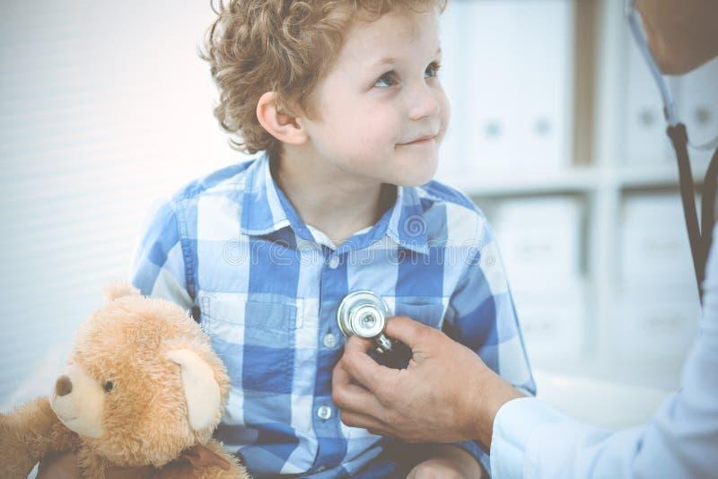 Doktor och t?lmodigt barn Unders?kande pys f?r l?kare Vanligt medicinskt bes?k i klinik care h?lsomedicinen arkivfoton