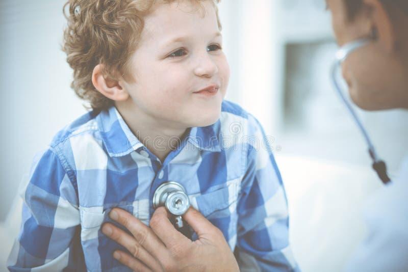 Doktor och t?lmodigt barn Unders?kande pys f?r l?kare Vanligt medicinskt bes?k i klinik care h?lsomedicinen royaltyfri foto