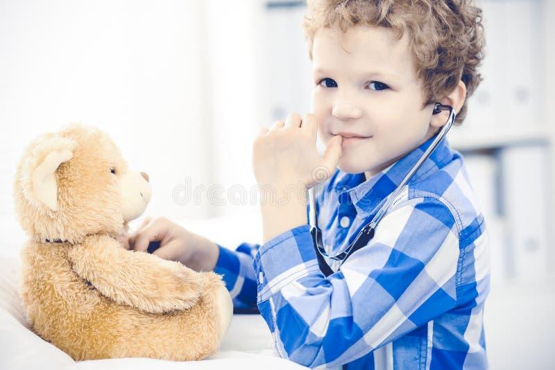 Doktor och t?lmodigt barn Unders?kande pys f?r l?kare Vanligt medicinskt bes?k i klinik care h?lsomedicinen royaltyfria bilder