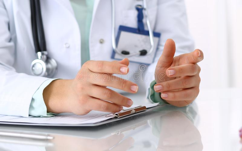 Doktor och t?lmodigt samtal, medan sitta p? skrivbordet i sjukhuskontoret, n?rbild av m?nskliga h?nder Medicin och h?lsa arkivbild