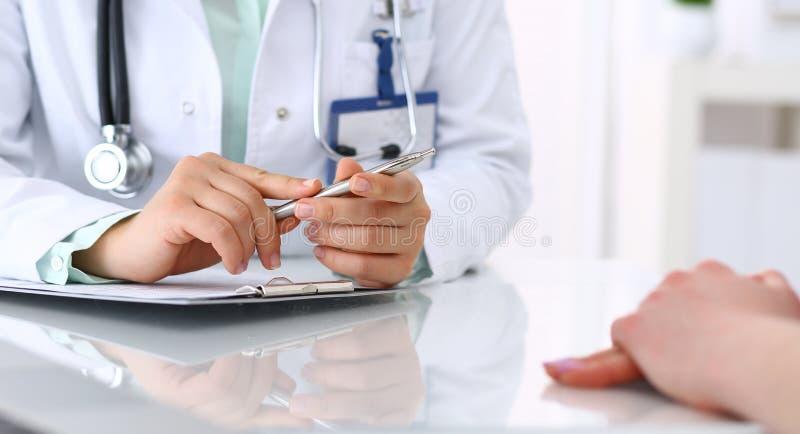 Doktor och t?lmodigt samtal, medan sitta p? skrivbordet i sjukhuskontoret, n?rbild av m?nskliga h?nder Medicin och h?lsa royaltyfria foton