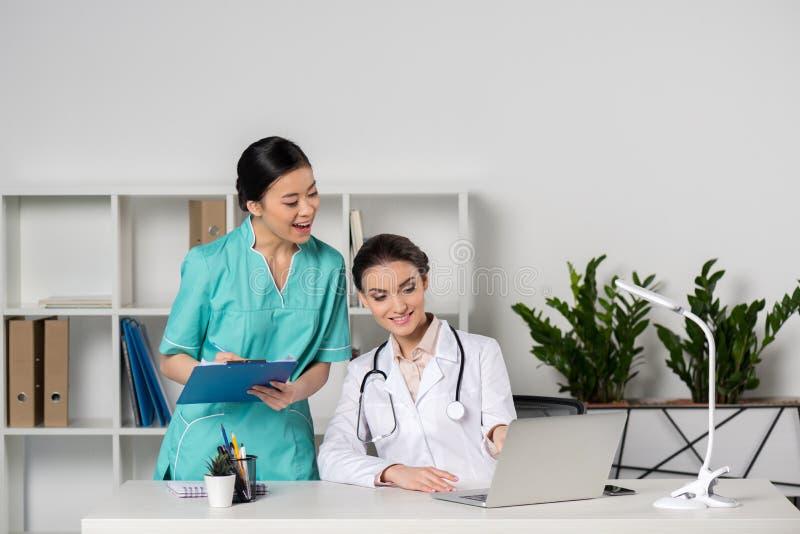 Doktor och ung asiatisk internist med diagnosen som ser bärbara datorn i klinik arkivbilder