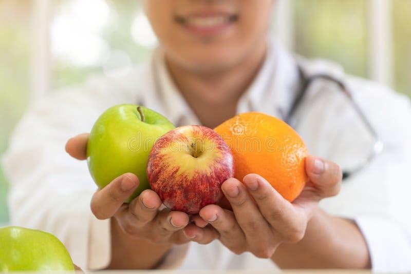 Doktor oder Ernährungswissenschaftler, die frische Frucht orange, rote und grüne Äpfel und Lächeln in der Klinik halten Gesunde D stockbild