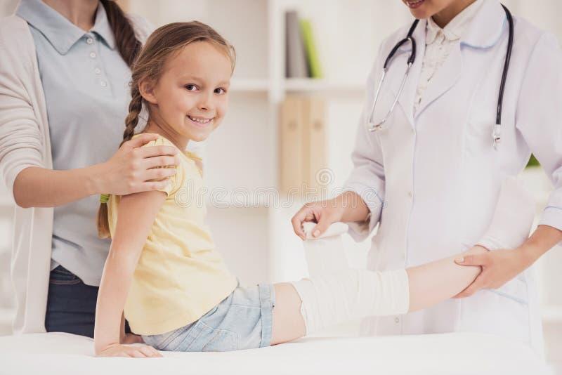 Doktor Rewinds Leg des kleinen Mädchens mit Verband lizenzfreie stockfotos