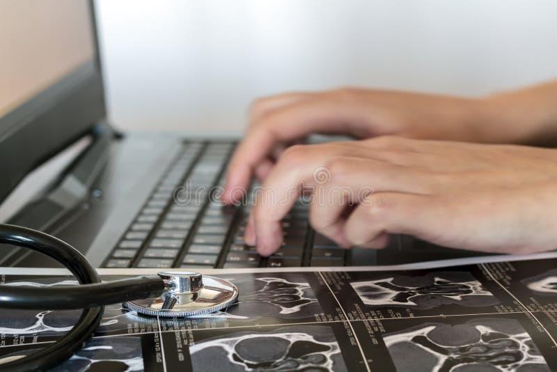 Doktor schreibt ärztlichen Attest über den Computer lizenzfreies stockbild