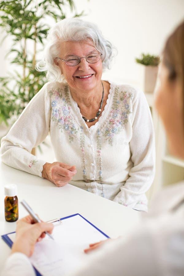 Doktor schreibt Verordnung für älteren Frauenpatienten stockbilder