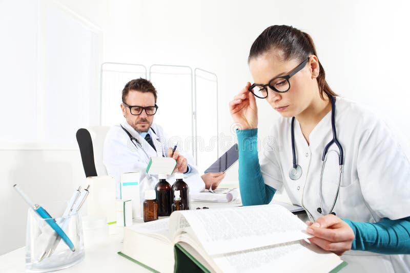 Doktor schreibt Verordnung mit der gelesenen Tablette und der Krankenschwester vor stockfotografie