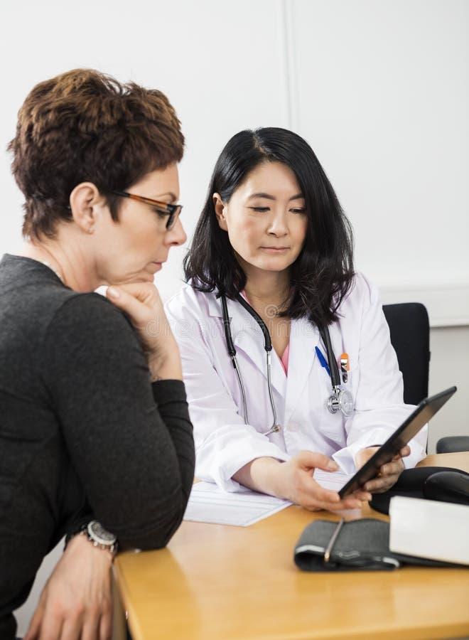 Doktor Showing Digital Tablet till den kvinnliga patienten arkivfoto