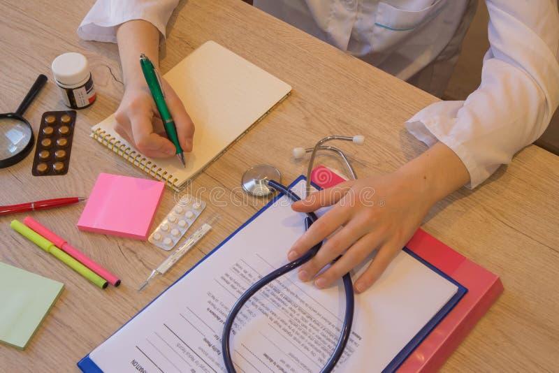 Doktor sitzt in einem Ärztlichen Dienst in der Klinik und schreibt Krankengeschichte lizenzfreie stockbilder