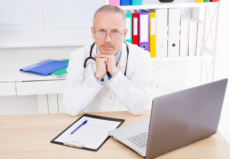 Doktor sitzt in einer Klinik am Tisch stockbilder